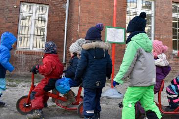 Kinder an der Haltestelle mit ihren Fahrzeugen.